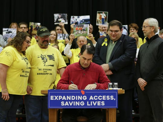 "Dillon's parents, Angel and George Mueller, left, watch Governor Scott Walker sign ""Dillon's Law"" at Mishicot High School as friends and family hold up hold up pictures of Dillon Mueller in remembrance Monday, Dec. 11, 2017, in Mishicot, Wis. Josh Clark/USA TODAY NETWORK-Wisconsin"