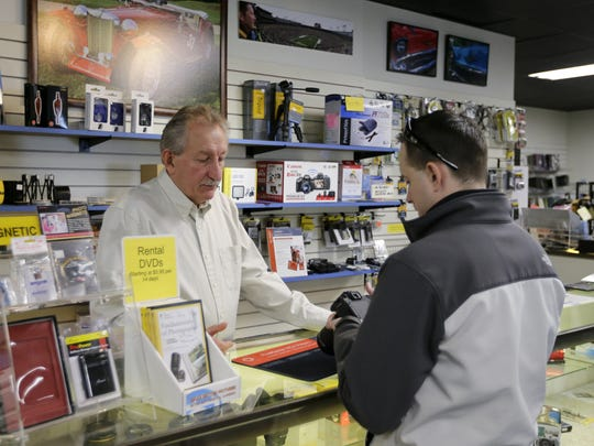 Todd Kresheck, owner of Lloyd's Photo & Digital, assists a customer in his store Feb. 13 in Manitowoc.