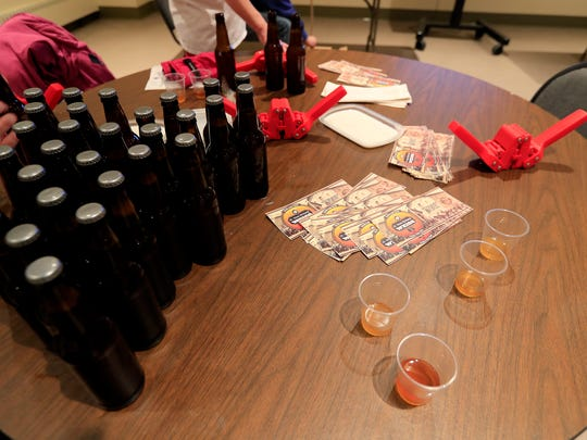 Samples of beer are shown as class participants bottle the beer brewed during a session of a Cellar Series class at the Neville Public Museum.