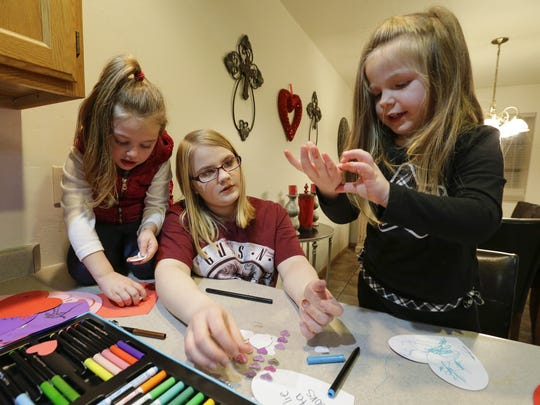 Skylar, 17, center, helps her younger sisters Anna, 4, left and Charlie, 3, with arts and crafts at their home Wednesday, Jan. 24, 2018, in Manitowoc. The older adopted siblings help care for the younger ones to help them adjust.