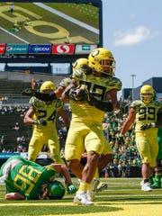 Oregon linebacker Kaulana Apelu intercepts a Justin Herbert pass and returns it for a touchdown Saturday.