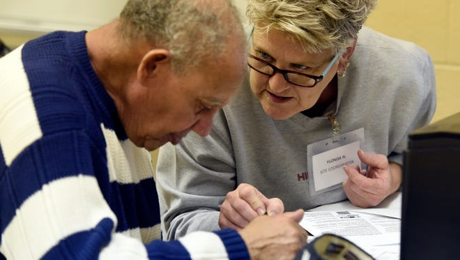 Owen Keye of Henderson gets help with his tax returns by Ylonda Nall through the Volunteer Income Tax Assistance (VITA) program at the Housing Authority of Henderson recently.  This is Nall's tenth year of volunteering in the program.