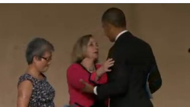 President Obama embraces Allison Crowther at the 9/11 museum dedication. At left is Ling Young, whom Welles Crowther helped to safety following the attacks.