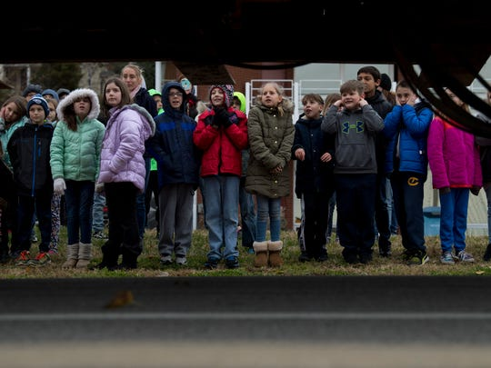 """Newburgh Elementary School students catch the passing of the """"little red brick house"""" as it is moved to its new home at the Newburgh Old Lock and Dam Tuesday morning."""