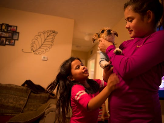 Diego gets an abundance of loving from Marrissiah Cuahua, 6, left, and her sister, Cecily, 10, at their aunt's home in Owensboro, Ky., Tuesday evening. The kids are staying with aunt, Jacqueline Linares of Owensboro, Ky., until they can obtain passports and then move to Mexico, a country they've never visited, to live with their father, Antonio Cuahua, who was deported after a U.S. Immigration and Customs Enforcement (ICE) raid recently.