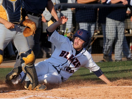 Blackman's Michael Dimartino (24) slides safely into home during a foul pop fly sacrifice during the game against Walker Valley, on Friday, May 19, 2017. Walker Valley catcher Hunter Shamblin waits at home for the ball.