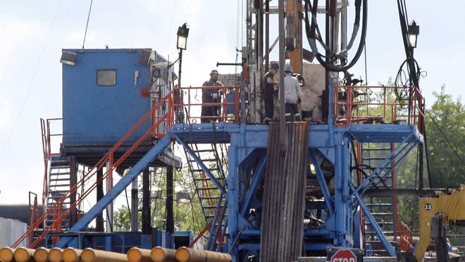 A crew works on a gas drilling rig at a well site for shale-based natural gas in Zelienople, Pa.