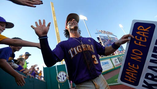 LSU's Kramer Robertson (3) celebrates with fans after LSU defeated Rice in an NCAA college baseball tournament regional game in Baton Rouge.
