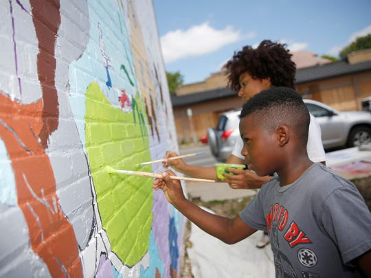 John Perry Nelson, age 8, a Sherman Park resident and Nyesha Stone, who was volunteering, work on painting the mural.