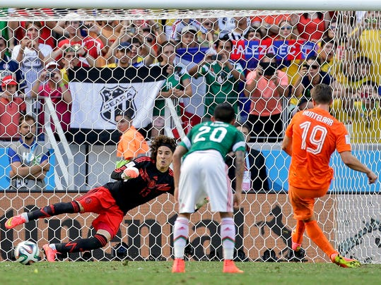 Mexico's goalkeeper Guillermo Ochoa can not stop a penalty shot by Netherlands' Klaas-Jan Huntelaar to score his side's second and winning goal during the World Cup round of 16 soccer match between the Netherlands and Mexico at the Arena Castelao in Fortaleza, Brazil, Sunday, June 29, 2014. The Netherlands defeated Mexico 2-1. (AP Photo/Felipe Dana)
