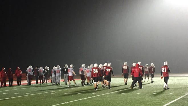 The St. John's defense practices in the rain Tuesday at Clemens Stadium.