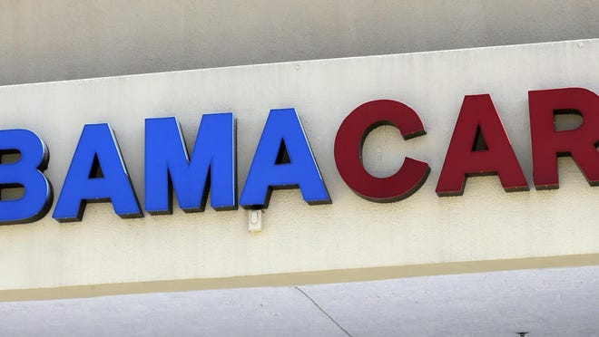 This May 11, 2017, file photo shows an Obamacare sign being displayed on the storefront of an insurance agency in Hialeah, Fla.
