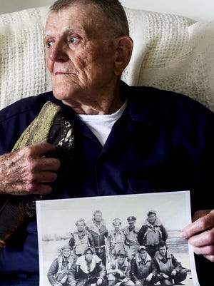 Robert Shroats, a World War II veteran who served as an engineer on a Boeing B-17 Flying Fortress, poses for a portrait with a picture of his old crew and the hat he wore as a bomber during his service. On Friday, Shroats will fly on a plane similar to the one he served on during the war.