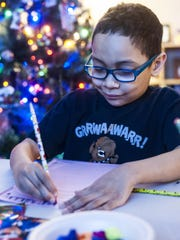 Trayson Harrell, 8, practices writing his name at a