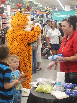 A Wal-Mart Neighborhood Market employee hands out samples of Oreo cookies during the store's grand opening Wednesday morning. The store opened after a ribbon cutting ceremony around 8 a.m.