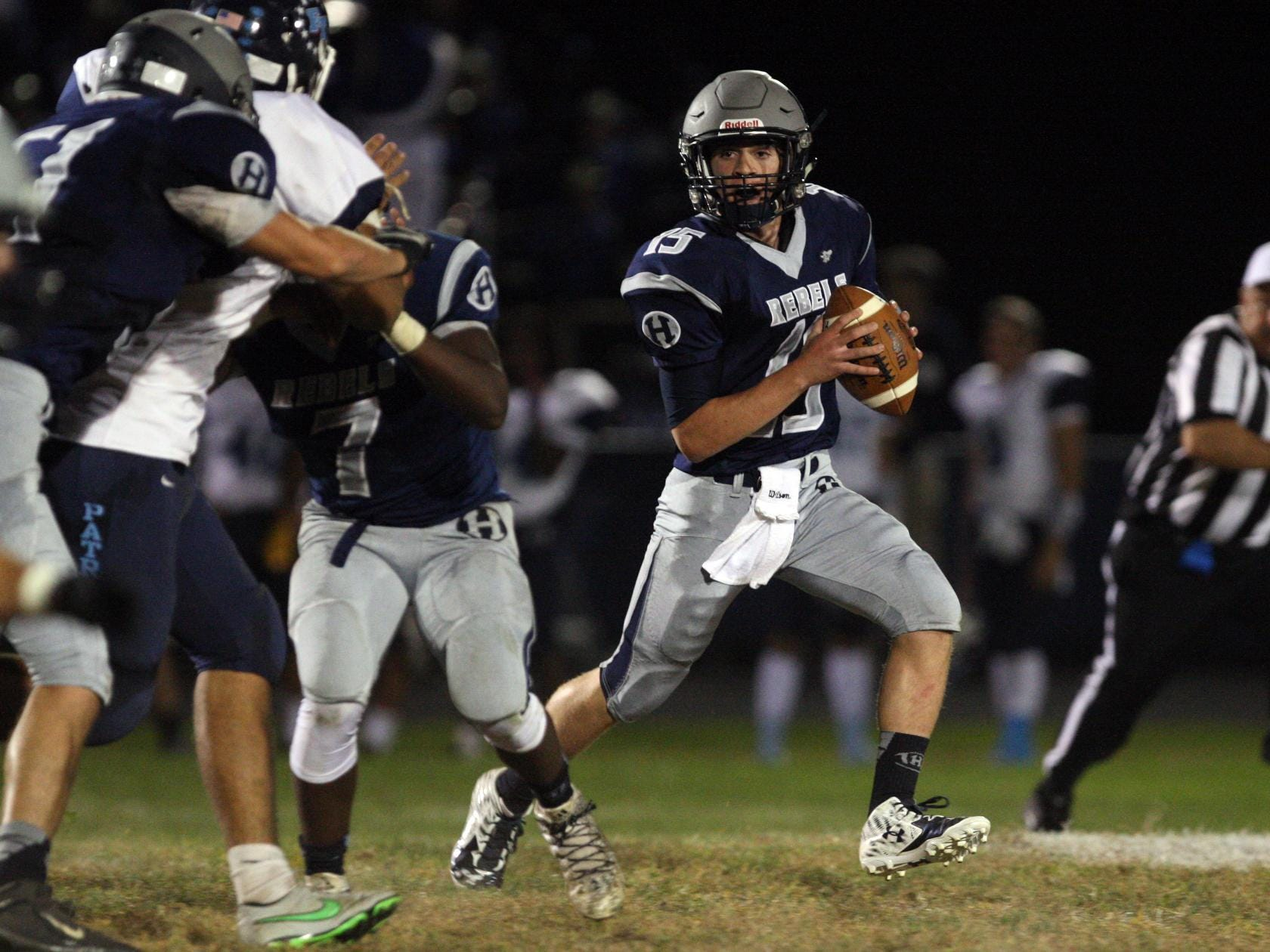 Quarterback Mark Iacobino, #15 Howell, scrambles with the ball as the Freehold Township defense chases him in a football game Friday, September 25, 2015, at Howell High School.