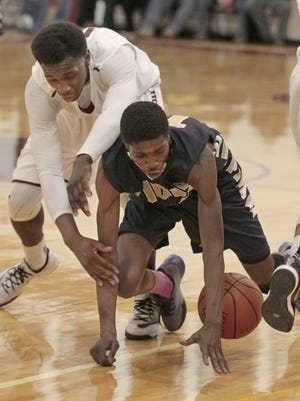 Leadership's Shabazz Mosley hits the floor as he fights for a loose ball with Aquinas' Melvin Grayson during the first half of their game Monday at Aquinas Institute.