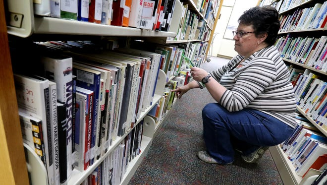 Library Specialist Colleen Yaggie pulls books from the Germantown Community Library stacks to be held for patrons or to be transferred to one of 33 other libraries in the four-county Monarch Library System.