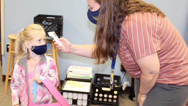 Bella Hardenbergh stands still as her temperature is taken by Jaime Adams at Gier Elementary School in Hillsdale.
