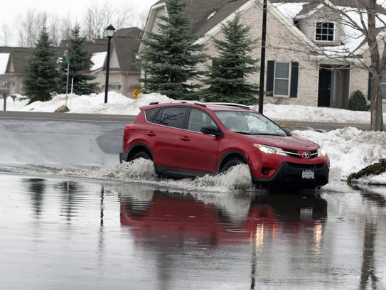 A resident drives through water from a swollen Cayuga