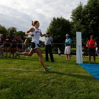 Menomonee Falls'  Kylee Wunschel hits the finish line a winner in the girls freshman-sophomore race of the Indians' own Coaches Classic Cross-Country Invite at Rotary Park on Aug. 25. He won in a time of 19:53.