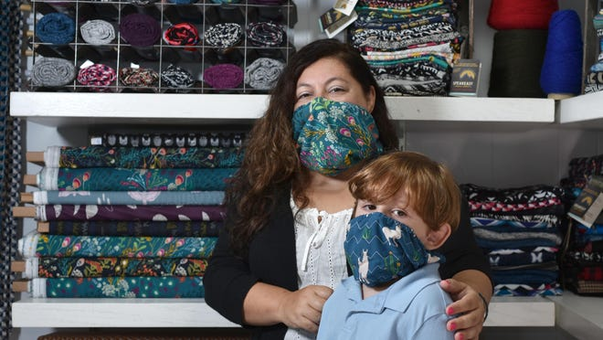 Bethany Salvon, owner of Speakeasy Travel Supply in Centerville, models her mask at her sewing studio with 4-year-old Joey Salvon-Berndt. Her mask design won the Massachusetts Technology Collaborative's inaugural COVID-19 Intrapreneur Challenge last month.