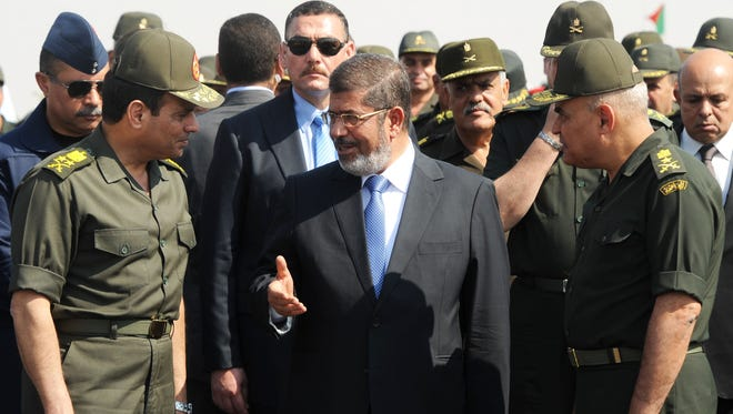 In this Oct. 10, 2012 file photo released by the Egyptian Presidency, Egyptian President Mohammed Morsi, center, speaks with Minister of Defense, Lt. Gen. Abdel-Fattah el-Sissi, left, at a military base in Ismailia, Egypt.