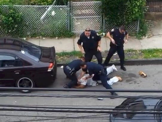 Elizabeth Police Officer Guido Quelopana puts his knee
