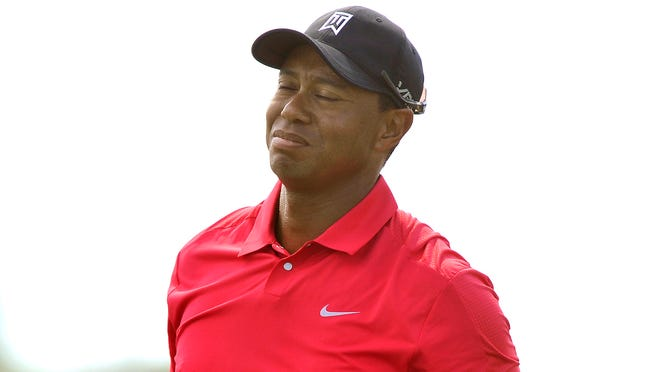 Tiger Woods grabs his back after his drive on the ninth hole and would later withdraw in the final round of The Honda Classic golf tournament on March 2.
