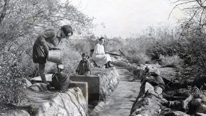 Helen, Barbara and Mabel Clatworthy getting water from the Tahquitz ditch on the grounds of The Desert Inn, circa 1925.