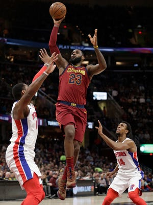 Cavaliers forward LeBron James, center, shoots between Pistons center Andre Drummond, left, and guard Ish Smith in the first half on Sunday, Jan. 28, 2018, in Cleveland.