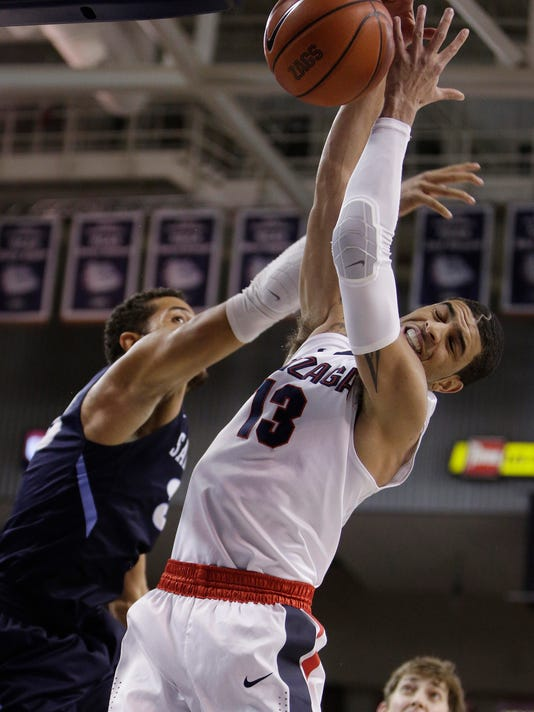 Gonzaga's Josh Perkins (13) and San Diego's Jito Kok go after a rebound during the first half of an NCAA college basketball game Saturday, Jan. 16, 2016, in Spokane, Wash. (AP Photo/Young Kwak)