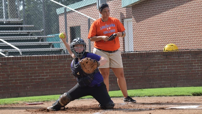 Erica Harwell (back), a former Louisiana College softball star and now head coach of the Alexandria Senior High softball team, watches Montgomery's Hannah Vercher as she catches during the Louisiana College Elite Softball Clinic held Tuesday.