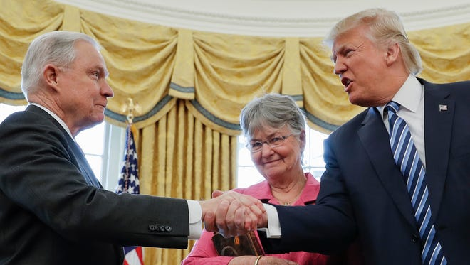 President Trump shakes hands with new Attorney General Jeff Sessions, accompanied by his wife, Mary, on Feb. 9, 2017.