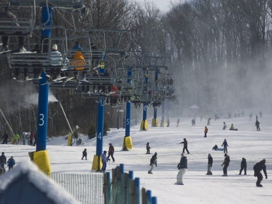 NEWS THE EVENING SUN -- SHANE DUNLAP Snowboarders and skiers take to the slopes at Ski Liberty on Sunday while lifts carry people to the top.