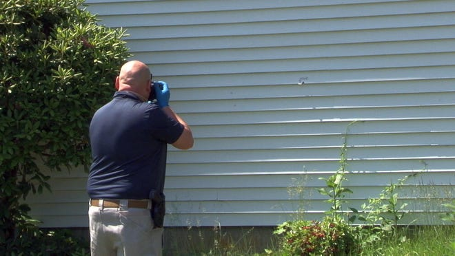A Grafton police officer photographs a bullet hole on the side of a house on Spring Hill Drive, where an armed invasion was reported Sunday morning.