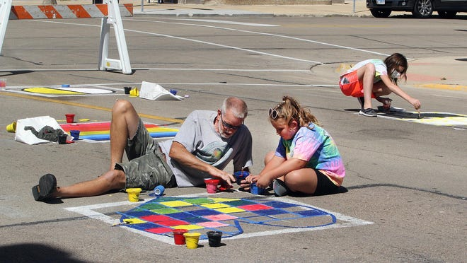 Dan Wessel, left, of Freeport gets creative with his granddaughter Lexi Hartman of Lanark on Saturday during Paint the Port in downtown Freeport.