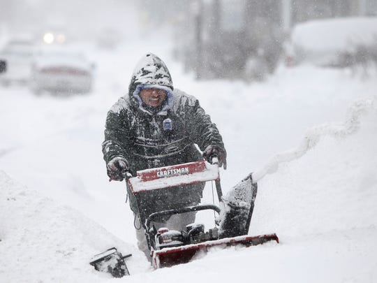 File photo: Robert Santiago helps clear his neighbors' driveways of snow on Avenue D in the city during a snowstorm.