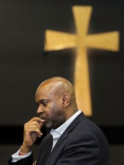 Rev. Damon Lynch III, pastor of New Prospect Baptist Church in Roselawn, listens as State Rep. Alicia Reece outlines a  $50 million program to combat crime and improve communities in the city.