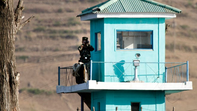 In this Wednesday, May 3, 2017 photo, a North Korean soldier looks through a pair of binoculars as he stands at a guard tower on the border near Chongsu in North Korea's North Pyongan Province, as seen from across the border in Dandong in northeastern China's Liaoning Province.