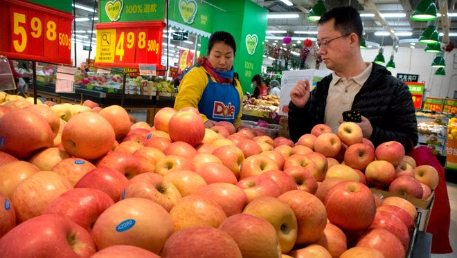 A woman wearing a uniform with the logo of an American produce company helps a customer shop for apples a supermarket in Beijing.