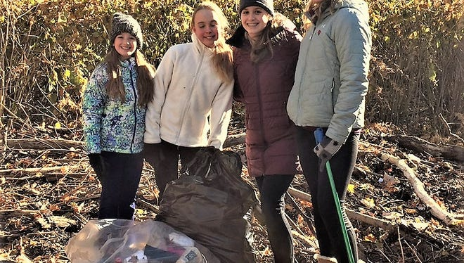 Thomas Jefferson School seventh-graders (from left) Mia D'Agostino, Ashtyn Grow, Miranda Peters, and Liz Jones take a break from their cleanup efforts at Potbelly's Riverside Cafe's 10th annual Fall Rockaway River Cleanup held last November. Join them again on Saturday to help the community.