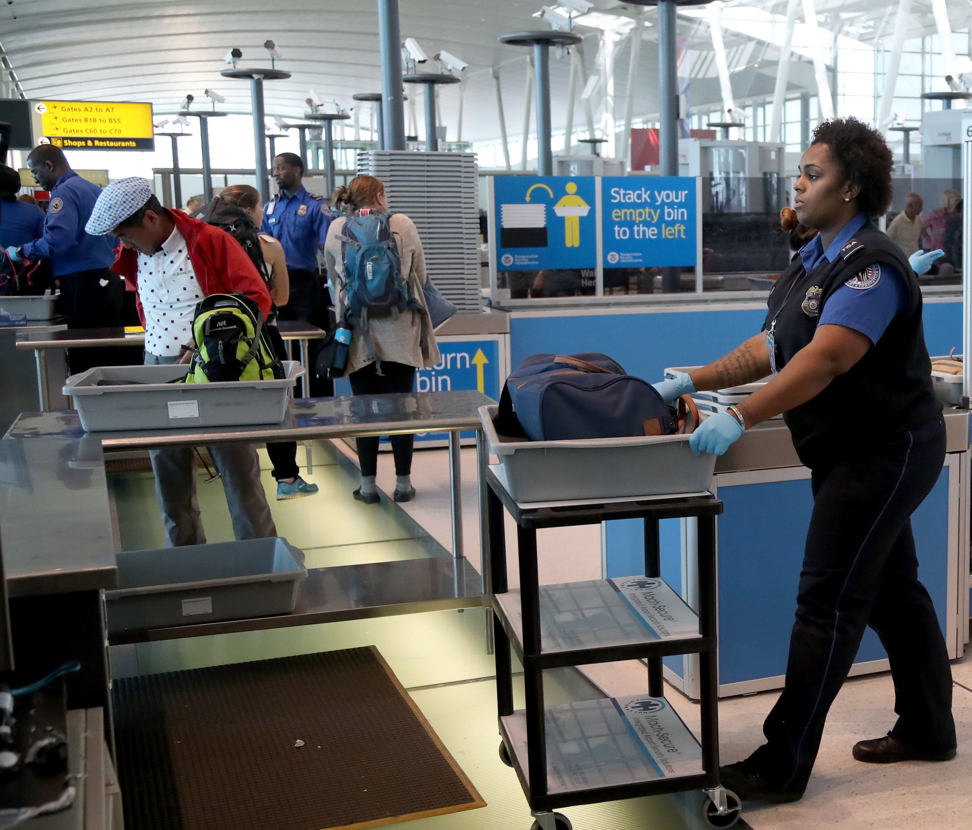 A Transportation Security Administration officer handles a bag for secondary screening at a new checkpoint with automated screening lanes at Terminal 4 at John F. Kennedy International Airport in Queens, New York on May 17, 2017.