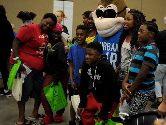 Kids pose for a photo with the Urban Air mascot at