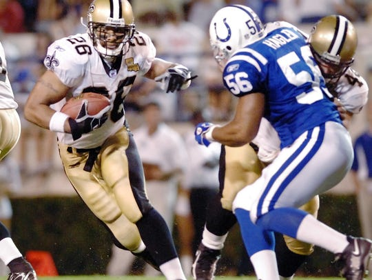 Saints running back Deuce McAllister (left) races around the Colt's Tyjuan Hagler.
