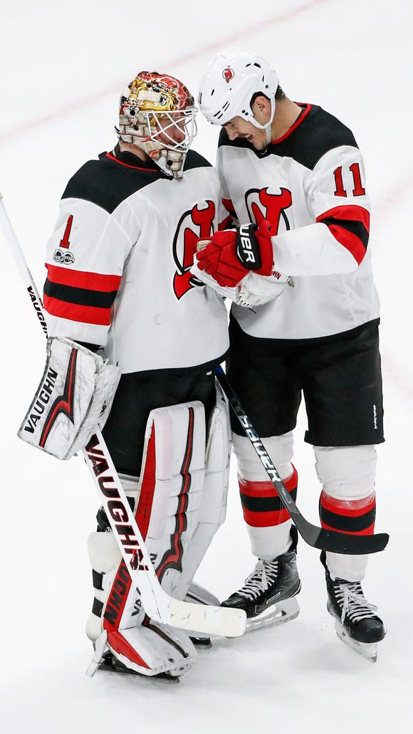 New Jersey Devils goalie Keith Kinkaid (1) celebrates with center Brian Boyle (11) at the end of an NHL hockey game against the Chicago Blackhawks Sunday, Nov. 12, 2017, in Chicago. Devils won 7-5. (AP Photo/Kamil Krzaczynski)