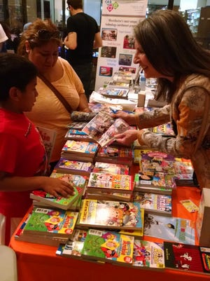 Archie Comics' Nancy Silberkleit talks with 7-year old Christopher Cervantes-Morales and his mother Yeni Morales-Diaz, of White Plains at Comic-Con 2 on Saturday.