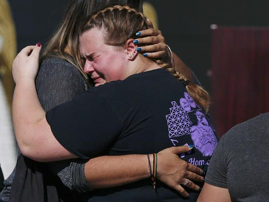Kieran Ahearn, right, cries on the shoulder of her friend, Lara Bortolotti, left, during a community vigil at Pine Trails Park, Thursday, Feb. 15, 2018, in Parkland, Fla., for the victims of the shooting at Marjory Stoneman Douglas High School. Nikolas Cruz, a former student, was charged with 17 counts of premeditated murder on Thursday. (AP Photo/Brynn Anderson)