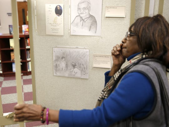 Joyce Johnson looks over the work of self-taught artist Harry M. Fordham III during a gallery exhibit at TCC's Library, including a work entitled 'My Heart and My Past: I Miss You', center, a copy of a drawing Fordham buried with his father after he passed.