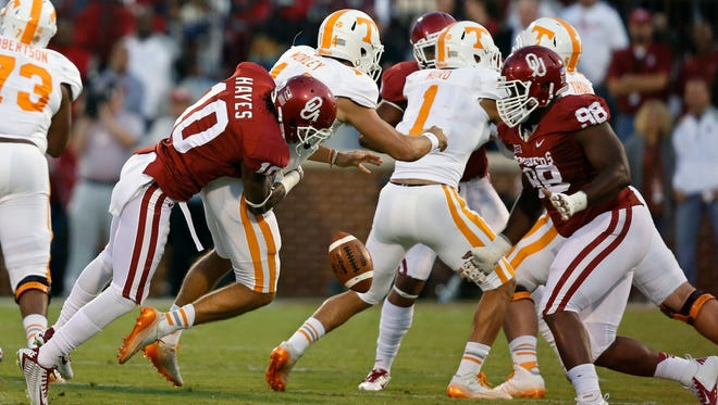 Tennessee quarterback Justin Worley (14) drops the ball as he is hit by Oklahoma safety Quentin Hayes (10) as Oklahoma defensive tackle Chuka Ndulue (98) moves in at right, in the first quarter of an NCAA college football game in Norman, Okla., Saturday, Sept. 13, 2014. Oklahoma recovered the ball. (AP Photo/Sue Ogrocki)